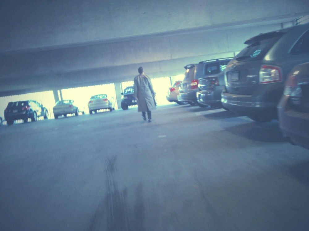 Following a man in a trench coat in a parking garage